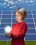 Boy with light bulb by solar panel