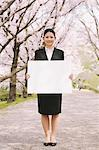 Businesswoman Holding Whiteboard With Cherry Blossoms In Background Stock Photo - Premium Rights-Managed, Artist: Aflo Relax, Code: 859-03884974