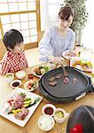 Parents and kids eating Japanese barbeque Stock Photo - Premium Royalty-Free, Artist: Photocuisine, Code: 670-03885852