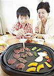 Grandmother and grandson eating Japanese barbeque Stock Photo - Premium Royalty-Free, Artist: Photocuisine, Code: 670-03885863