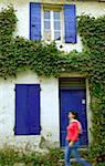 Arles; Bouches du Rhone, France; A young woman walking in front a brightly coloured  house. Stock Photo - Premium Rights-Managed, Artist: AWL Images, Code: 862-03887773