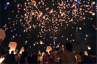 release - Thailand, Chiang Mai, San Sai.  Revellers launch khom loi (sky lanterns) into the night sky during the Yi Peng festival.  The ceremony is a Lanna (northern Thailand) tradition and coincides with Loy Krathong festivities.  The khom loi are released in the belief that grief and misfortune will float await them, bringing good luck. Stock Photo - Premium Rights-Managednull, Code: 862-03889859