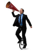 Businessman Riding Unicycle and Yelling into Megaphone Stock Photo - Premium Rights-Managednull, Code: 700-03891176