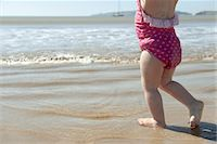 Toddler girl walking in surf at the beach, low section Stock Photo - Premium Royalty-Freenull, Code: 632-03897987