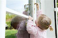 Toddler girl reaching to open door Stock Photo - Premium Royalty-Freenull, Code: 632-03898075