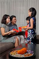 singapore traditional costume lady - Chinese parents giving red envelopes (Hong Bao) to daughters during Chinese New Year Stock Photo - Premium Rights-Managednull, Code: 849-03901160