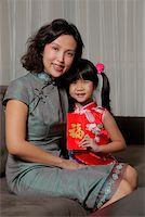 singapore traditional costume lady - Mother holding daughter with red envelope (Hong Bao) Stock Photo - Premium Rights-Managednull, Code: 849-03901233