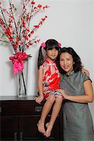 singapore traditional costume lady - Chinese mother and daughter wearing Cheongsams sitting near flowers Stock Photo - Premium Rights-Managednull, Code: 849-03901271