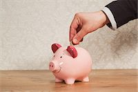 Man inserting pound coin into piggy bank Stock Photo - Premium Royalty-Freenull, Code: 614-03903063