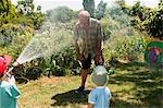 Grandsons spraying grandfather with hosepipe Stock Photo - Premium Royalty-Free, Artist: Westend61, Code: 614-03903157