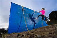 forward - Woman climbing wall using rope in obstacle course Stock Photo - Premium Royalty-Freenull, Code: 6102-03905979