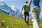 Backview of Couple Hiking using Walking Sticks, Bernese Oberland, Switzerland