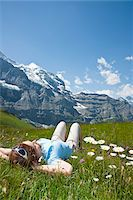 Woman Lying on Grass on Mountain Side, Bernese Oberland, Switzerland Stock Photo - Premium Royalty-Freenull, Code: 600-03907131