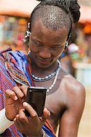 Masai Man in Traditional Dress Using Cell Phone, Zanzibar, Tanzania Stock Photo - Premium Rights-Managednull, Code: 700-03907391