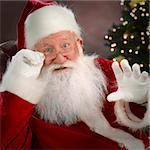 Santa Claus, waist up, indoor studio shot, christmas decoration in background, waving hand, focus on foreground Stock Photo - Royalty-Free, Artist: scotthancock, Code: 400-03919056