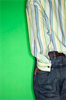 Back view torso of African-American teen boy with hand in back pocket of jeans standing against green background. Stock Photo - Royalty-Freenull, Code: 400-03921362