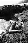 Young nude Asian woman partially submerged in water lying face down on rocky coast.