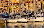 The Vieux Port (old port) in the city of Cannes in the French riviera, as the first rays of the morning sun illuminate the marina and the buildings behind the boats. Stock Photo - Royalty-Free, Artist: akarelias, Code: 400-03928268