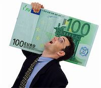 Happy businessman carrying a big hundred euro Stock Photo - Royalty-Freenull, Code: 400-03932248