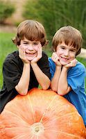 Two Boys Resting on a Huge Pumpkin Stock Photo - Royalty-Freenull, Code: 400-03936487
