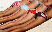 Four girls in bikini lying on the sand Stock Photo - Royalty-Freenull, Code: 400-03940461