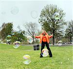 Girl playing with bubbles in a park Stock Photo - Royalty-Free, Artist: barsik, Code: 400-03941861