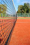tennis court under blue sky, the net as leading line (wide angle)