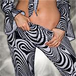 Caucasian woman in sexy clothing with hands on pants.