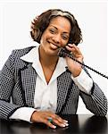 Businesswoman sitting at desk holding telephone receiver to ear smiling. Stock Photo - Royalty-Free, Artist: iofoto, Code: 400-03949207