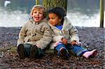 A little blond boy and a mixed race girl sitting resting at the base of a tree. Stock Photo - Royalty-Free, Artist: darrenbaker, Code: 400-03964775