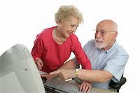 A senior lady teaching a senior man how to use the computer. He has a question.  Isolated on white. Stock Photo - Royalty-Freenull, Code: 400-03969316