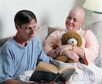 A man volunteering to read the bible to a cancer patient. (focus is on the woman's face) Stock Photo - Royalty-Free, Artist: lisafx, Code: 400-03972468