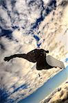 Snowboarder launching off a jump; vertical orientation, warm afternoon light.