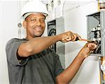 Handsome african american electrician working on a breaker panel.  Model is an actual electrician performing work according to industry safety and code standards. Stock Photo - Royalty-Free, Artist: lisafx, Code: 400-03988979