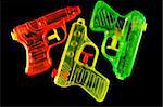 Three toy squirt guns isolated on a black mirrored background Stock Photo - Royalty-Free, Artist: karimala, Code: 400-03992646