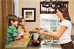 Hispanic mother handing healthy breakfast to young children in home kitchen. Stock Photo - Royalty-Free, Artist: iofoto, Code: 400-03999344