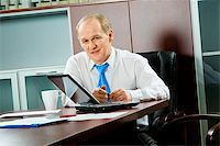 Portrait of a senior businessman sitting at the table with open laptop, papers, cup and two pens on it Stock Photo - Royalty-Freenull, Code: 400-04005385