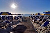 Empty beach with umbrellas and sun shortly after the sunrise Stock Photo - Royalty-Freenull, Code: 400-04010263