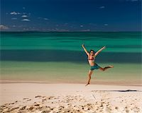 Young woman jumping on white sand beach by turquoise waters on tropical island Stock Photo - Royalty-Freenull, Code: 400-04011970