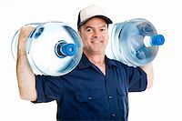 Strong water delivery man smiling as he carries two full five gallon water jugs on his shoulders.  Isolated on white. Stock Photo - Royalty-Free, Artist: lisafx, Code: 400-04023057