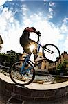 Freestyle young male rider performing a jump, urban area. Fish-eye lens. Stock Photo - Royalty-Free, Artist: rcaucino, Code: 400-04023545
