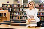 Image of teacher standing near table with books on it in the library Stock Photo - Royalty-Free, Artist: pressmaster, Code: 400-04027352