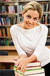 Portrait of young woman keeping her arms on the top of book stack in the library Stock Photo - Royalty-Free, Artist: pressmaster, Code: 400-04030571