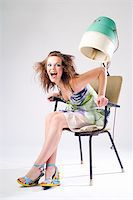 Expressive pretty girl in dress with hair dryer Stock Photo - Royalty-Freenull, Code: 400-04030780