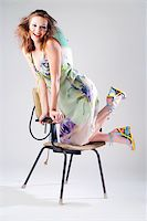 Expressive pretty girl in dress with hair dryer Stock Photo - Royalty-Freenull, Code: 400-04030782