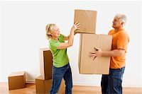 Middle-aged man holding cardboard moving boxes while woman places one on stack. Stock Photo - Royalty-Free, Artist: iofoto, Code: 400-04039985