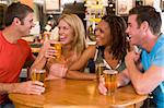 Group of young friends drinking and laughing in a bar Stock Photo - Royalty-Free, Artist: MonkeyBusinessImages, Code: 400-04040279