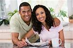 Couple in kitchen with newspaper and coffee smiling Stock Photo - Royalty-Free, Artist: MonkeyBusinessImages, Code: 400-04043676