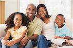Family sitting in living room smiling Stock Photo - Royalty-Free, Artist: MonkeyBusinessImages, Code: 400-04043796