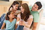 Family sitting in living room smiling Stock Photo - Royalty-Free, Artist: MonkeyBusinessImages, Code: 400-04043968